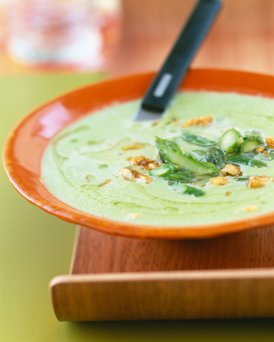Cream of asparagus soup with crushed walnuts