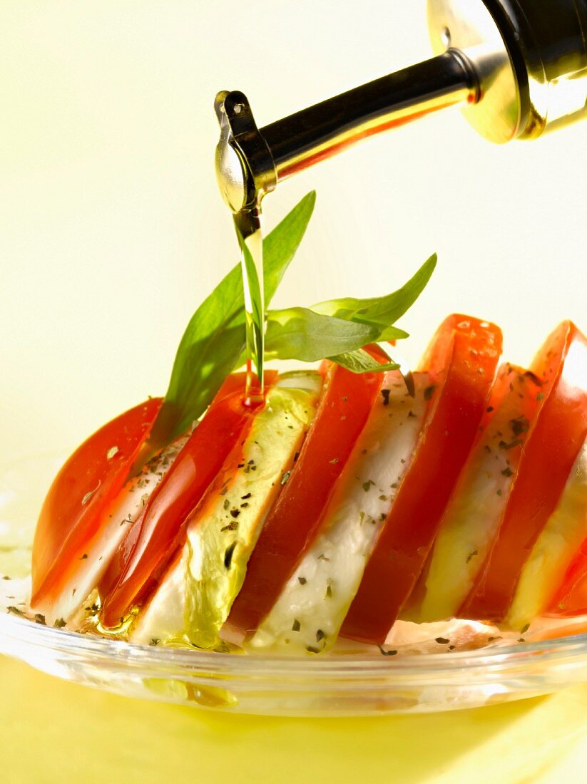 Pouring olive oil onto a dish of tomatoes and mozzarella
