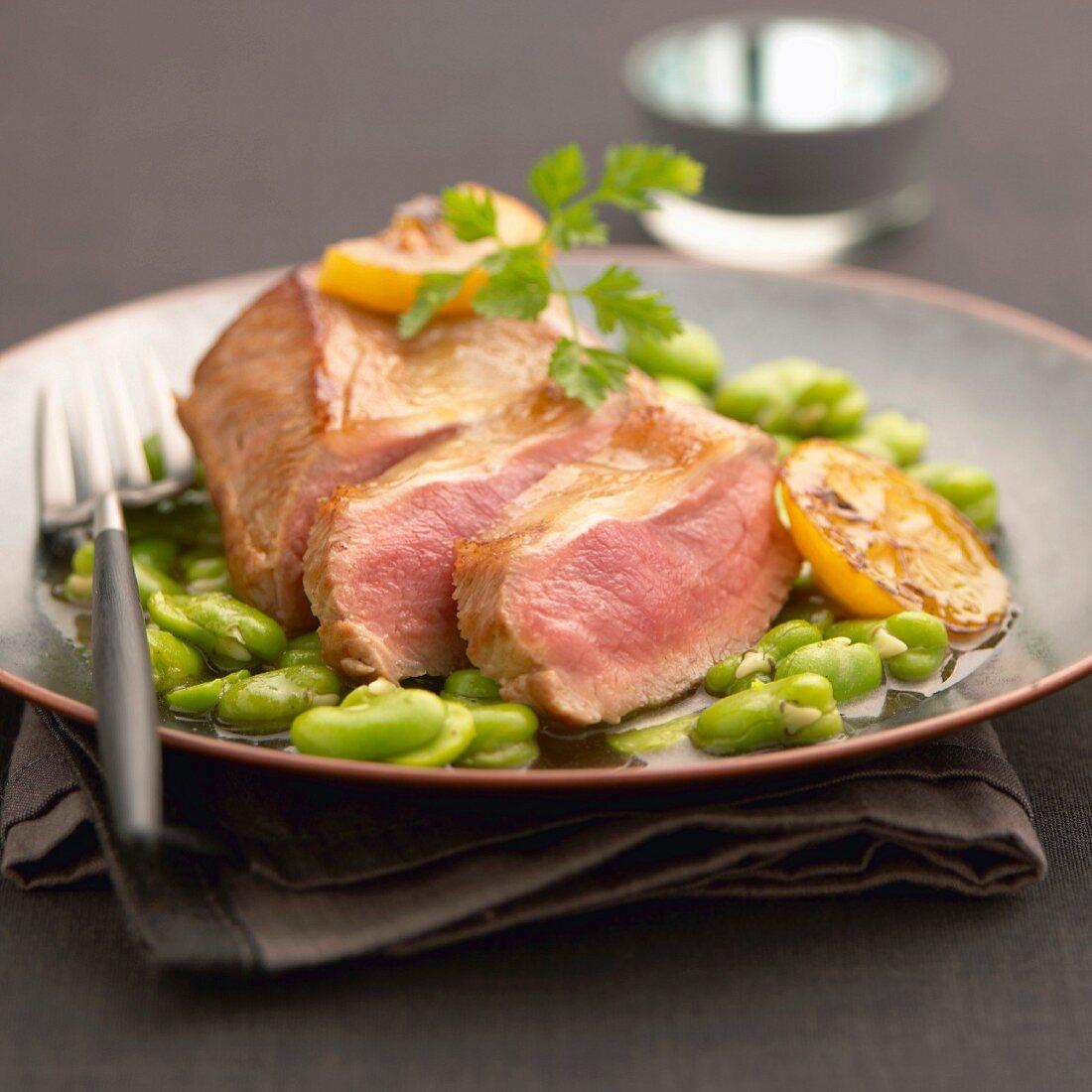Gebratenes Lammfleisch auf frischen Ackerbohnen