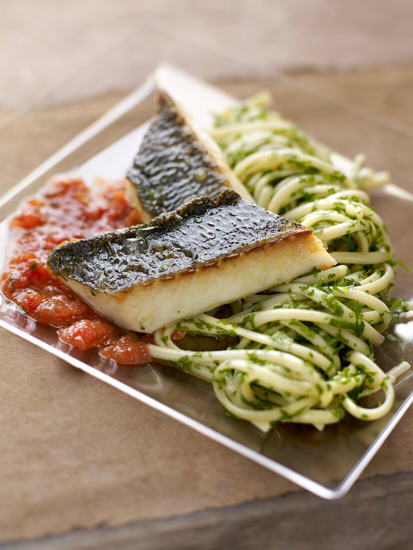 Piece of bass with tomato puree and spaghettis with herbs