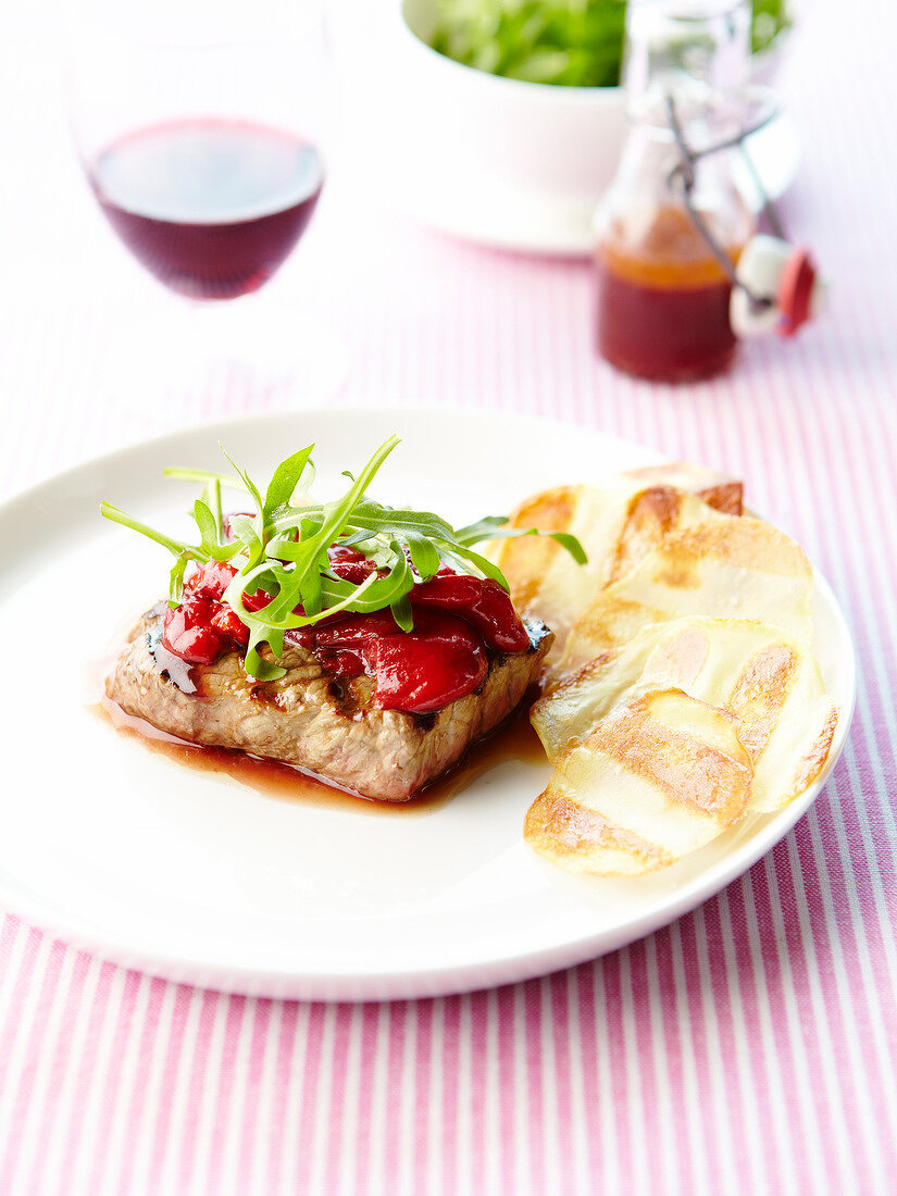 Grilled beef steak with stewed red peppers and crisps