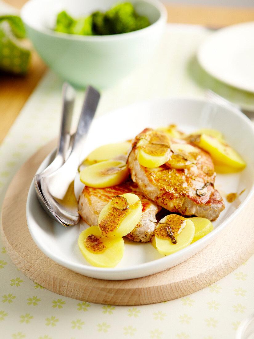 Pork chops with sauteed potatoes,traditional mustard and tarragon sauce