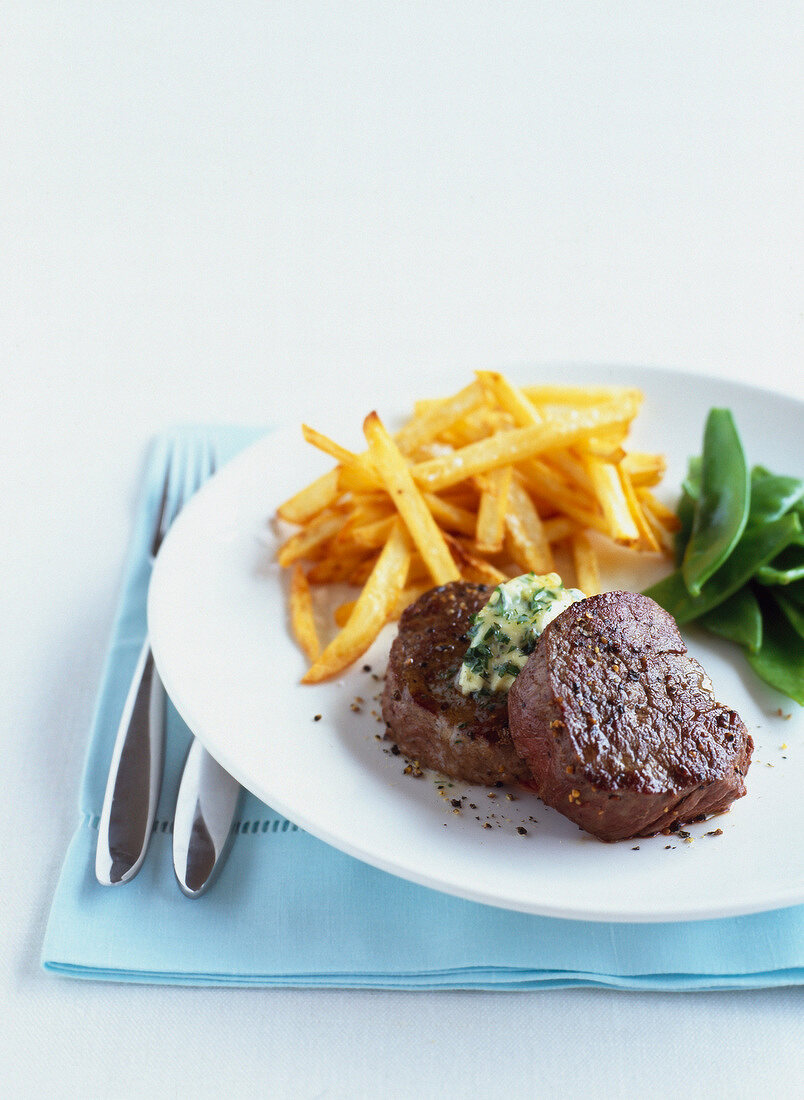 Beef fillets with french fries and sugar peas
