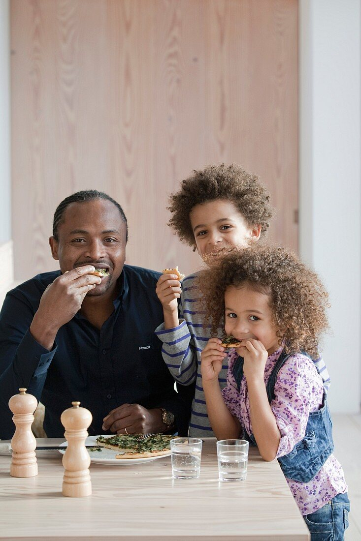 Father and children eating pizza together