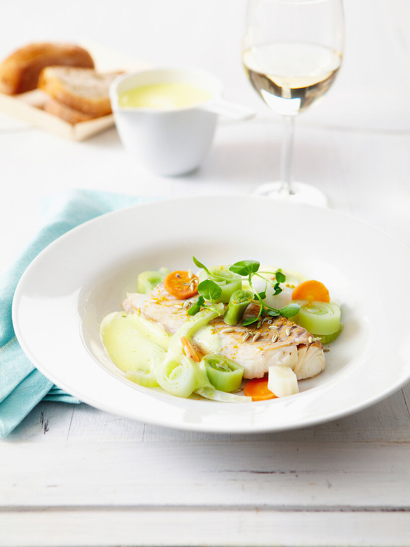 Poached cod fillet with leeks and carrots