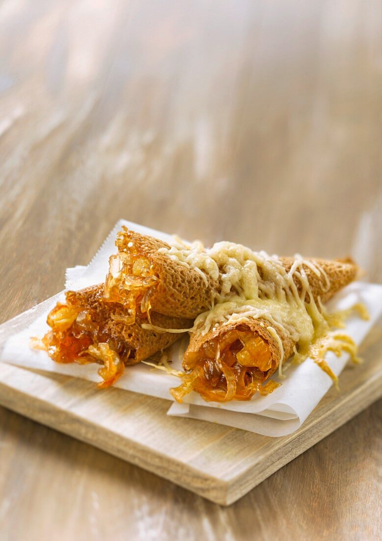 Rolled buckwheat crepes with confit raisins and topped with grilled gruyere
