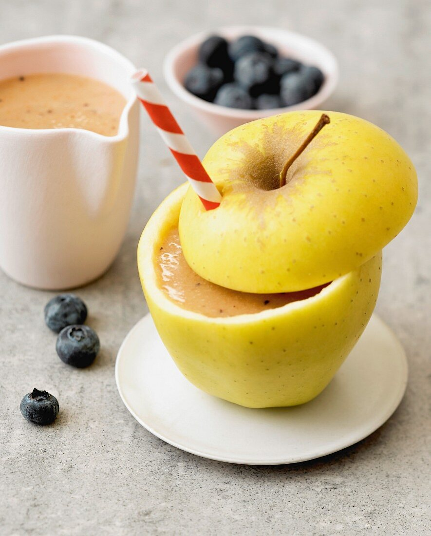 Apple, carrot and blueberry smoothie served in a golden apple