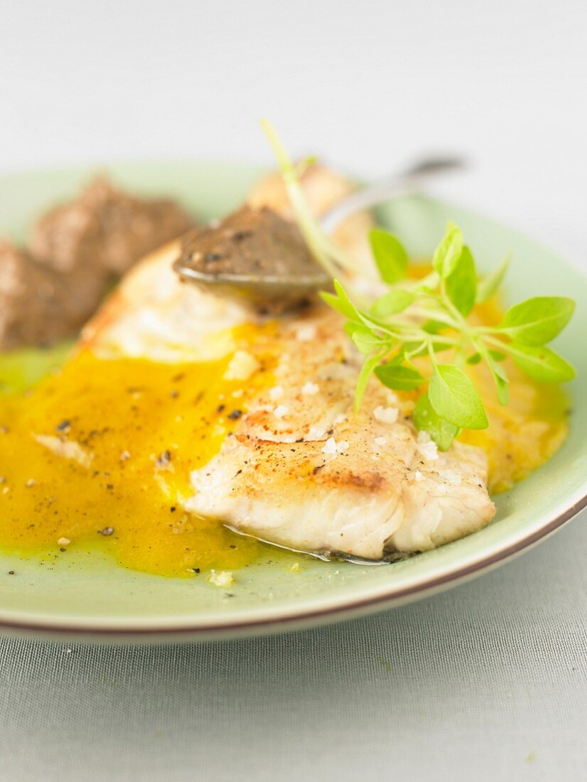 Roasted bass fillet with orange sauce and tapenade