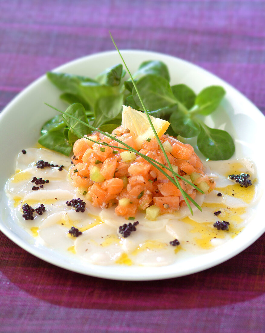 Salmon tartare on a bed of thinly sliced scallops