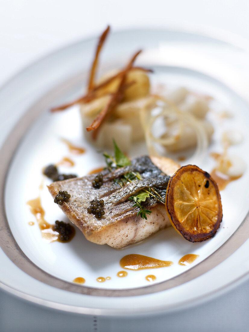 Piece of sea bass with lemon caramel and caviar