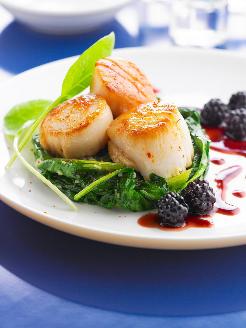 Pan-fried scallops on a bed of spinach and rice,blackberry sauce