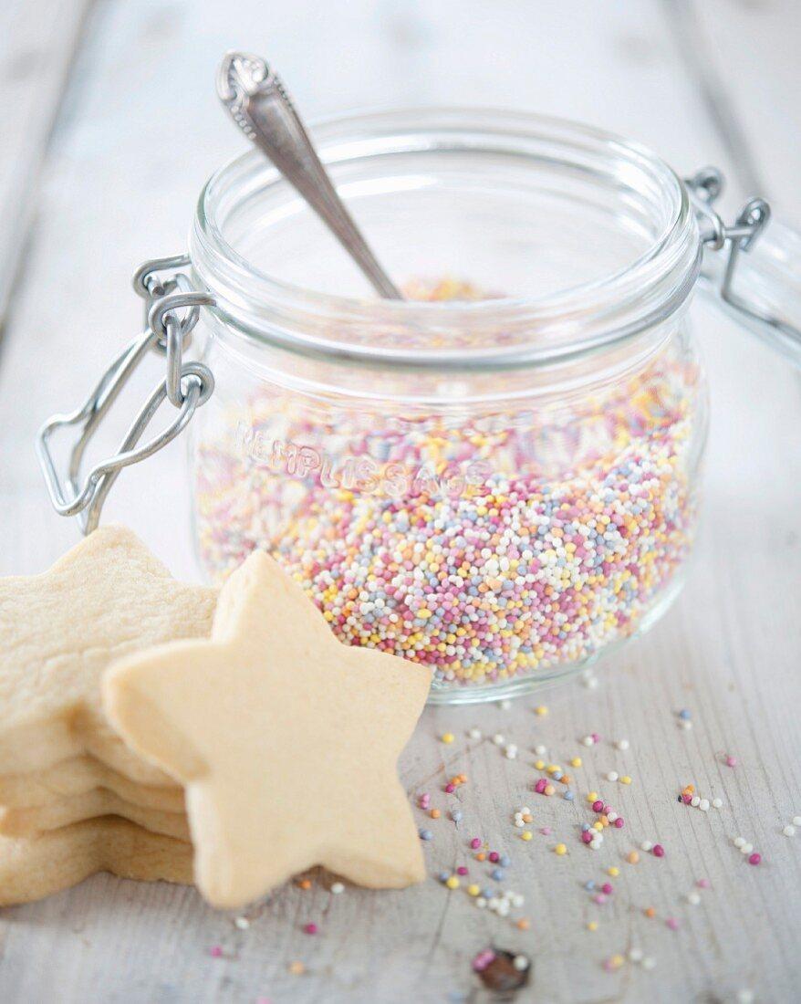 Jar of multicolored sugar drops and shortbread cookies