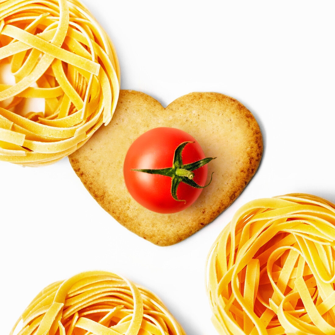 Heart-shaped biscuit witha cherry tomato and tagliatelle nests