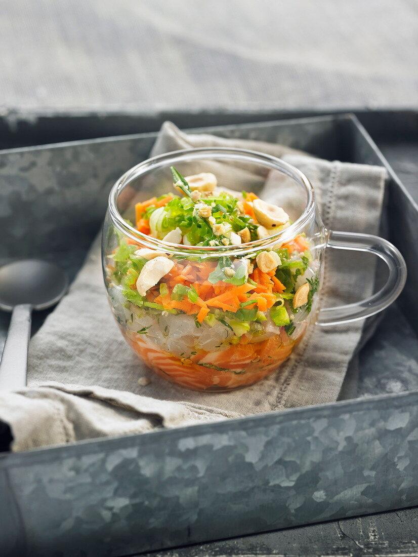 Tatar vom Lachs, Adlerfisch und Gemüse mit Mandelöl, im Gläschen serviert