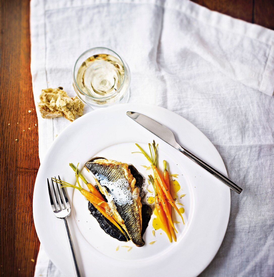 Sea bass fillets with onions, smoked milk, squid ink cream and carrots with orange
