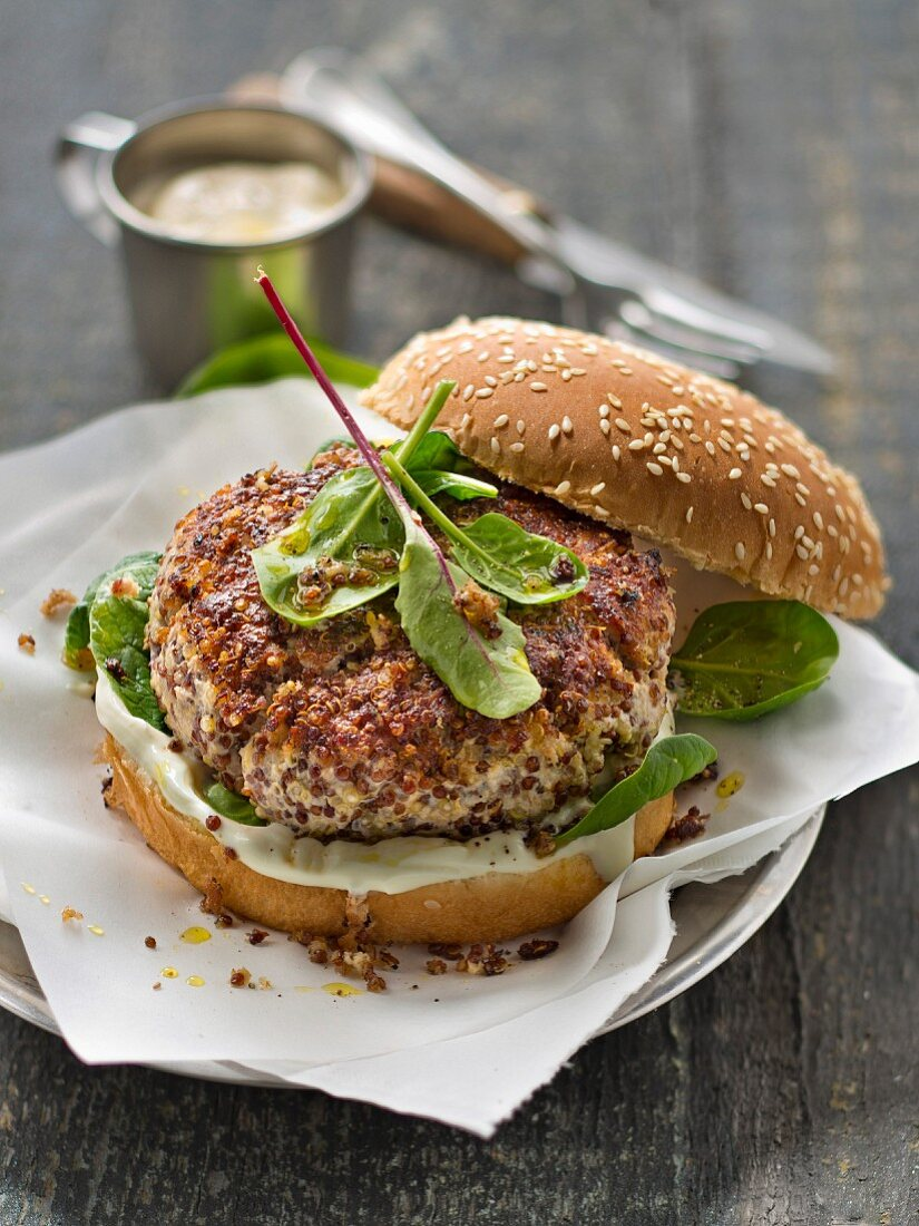 Veal and quinoa burger with baby spinch and white sauce