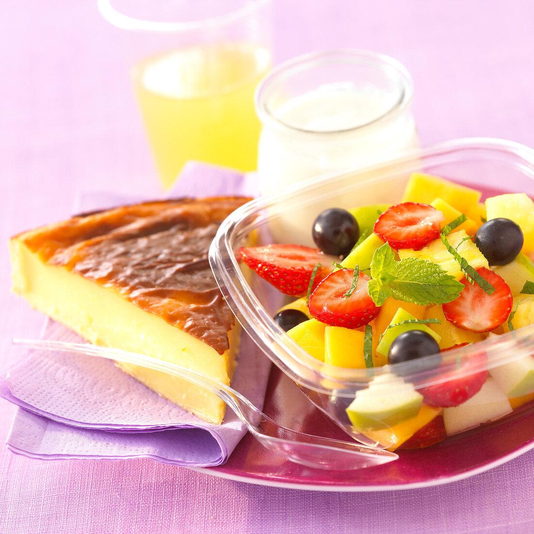 Fresh fruit salad,a slice of flan,a glass of orange juice and a yoghurt
