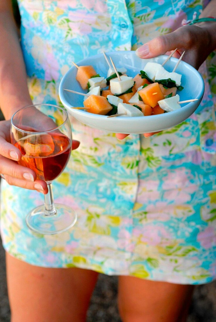 Woman holding a dish of melon-mozzarella-basil bites and a glass of rosé
