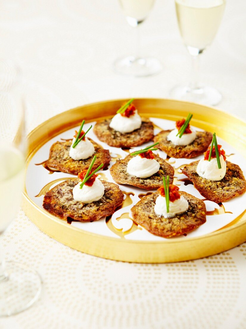 Homemade parmesan and herb tuiles,whipped cream with chives and confit tomato