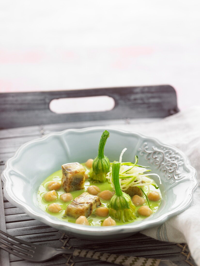 Pesto soup with chickpeas, zucchini flowers and eggplants