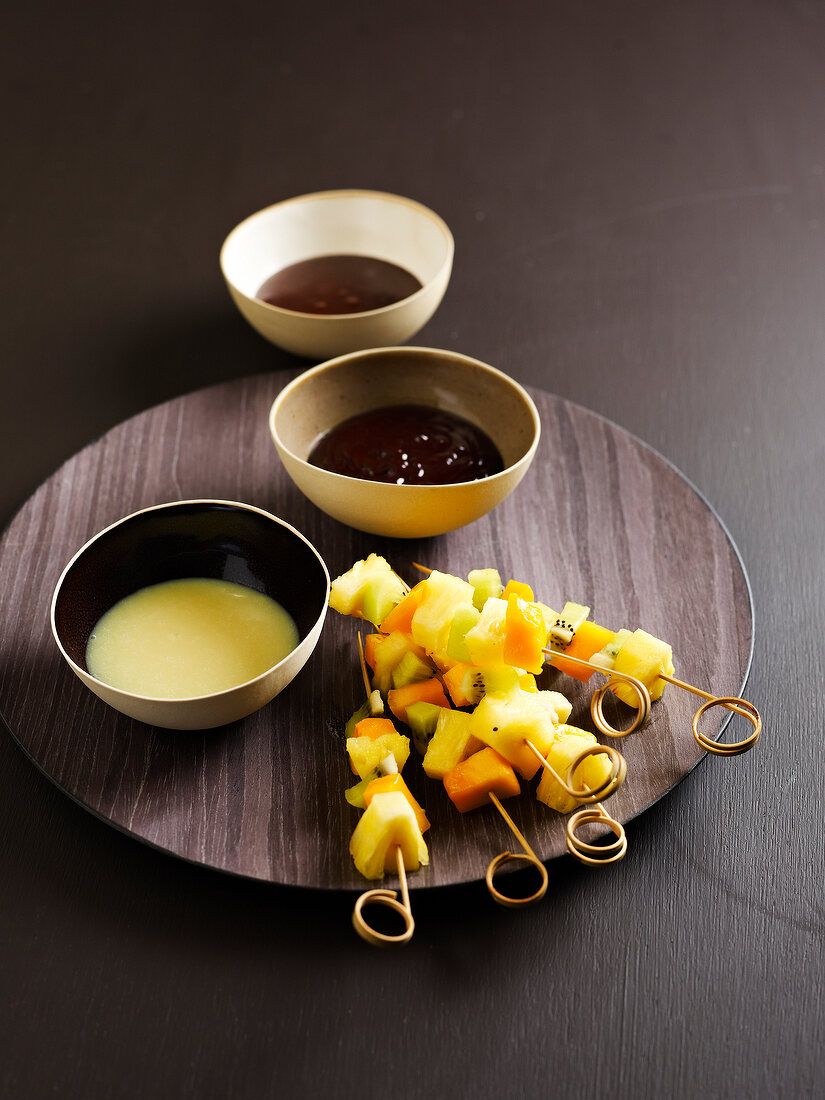Exotic fruit brochettes with three different chocolate sauces