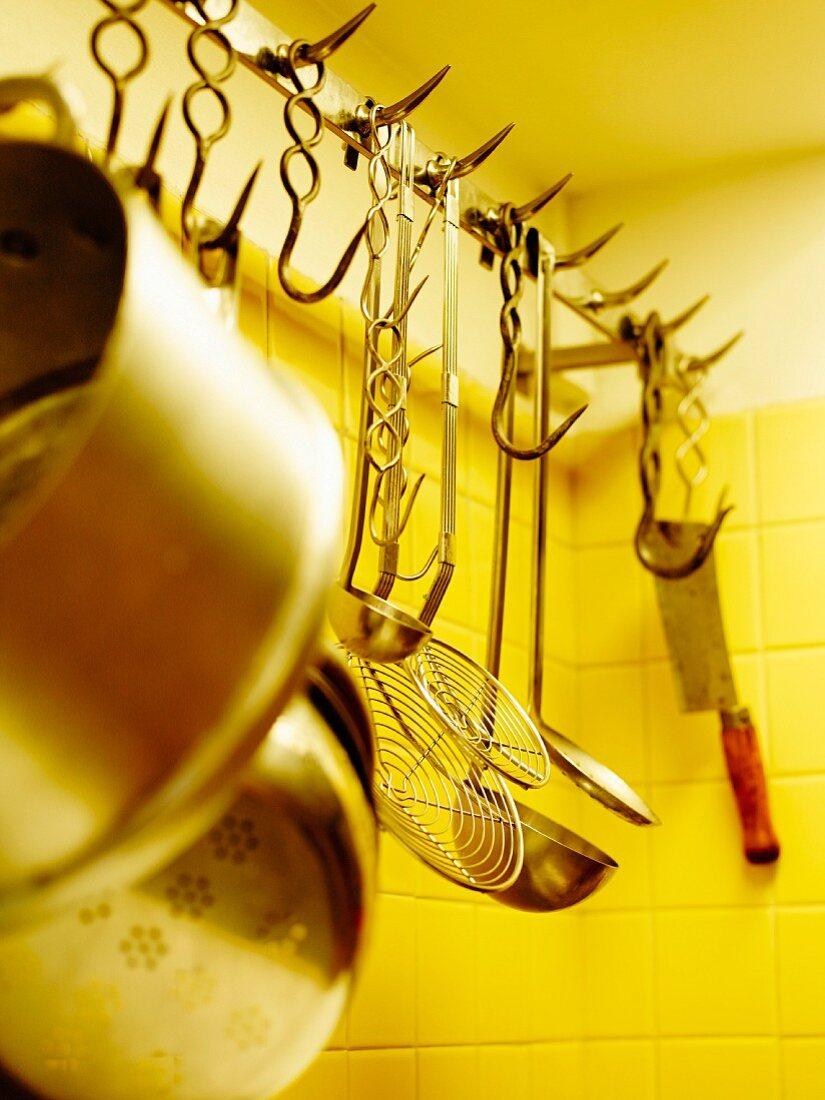 Hängende Kochutensilien in einer Küche
