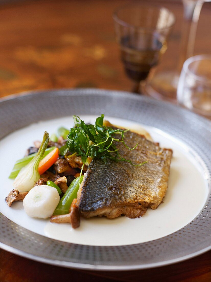 Bass fillet grilled with Champagne,spring vegetables and wild mushrooms