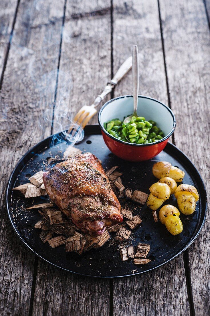 Knuckle of ham roasted with herbs,cardoons,sauteed potatoes and broad beans