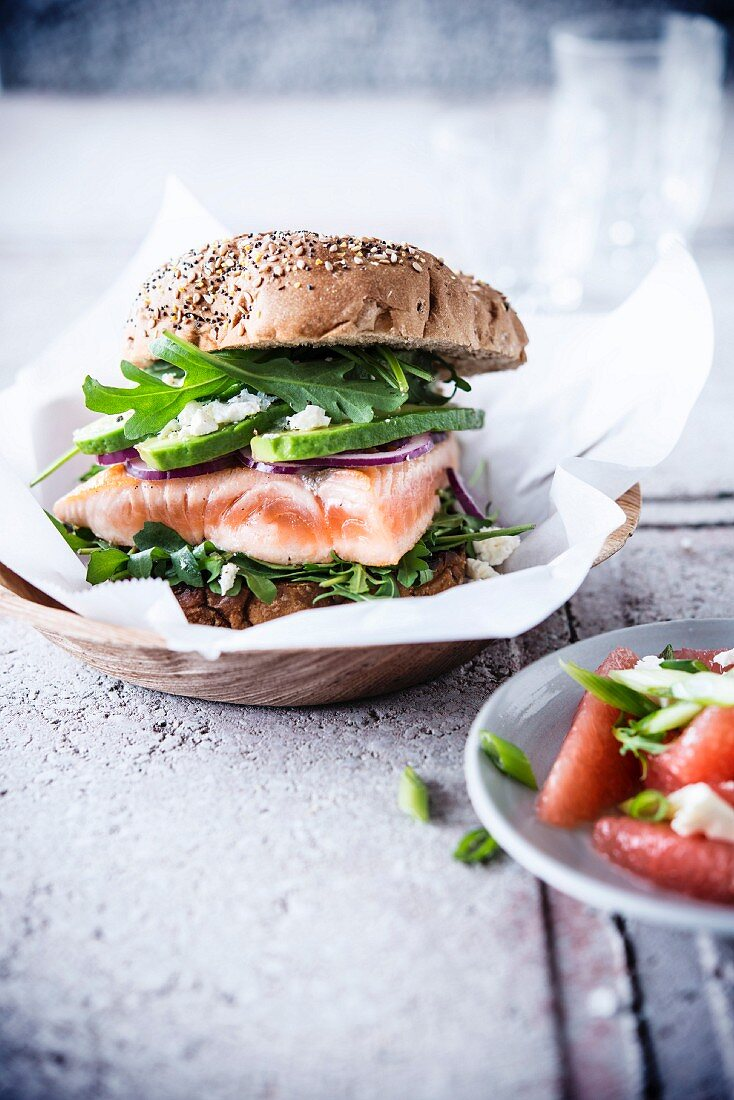 Salmon burger with avocado, rocket and feta cheese with a pink grapefruit salad