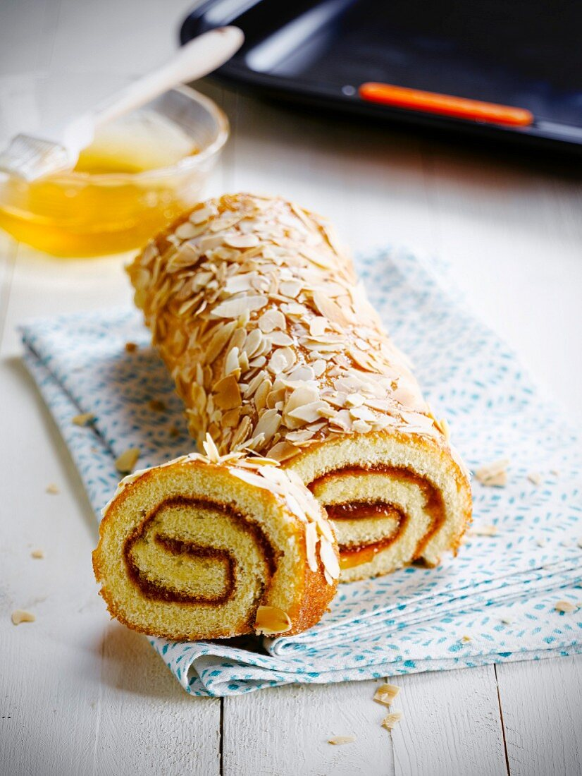 Apricot jam rolled sponge cake coated with thinly sliced grilled almonds