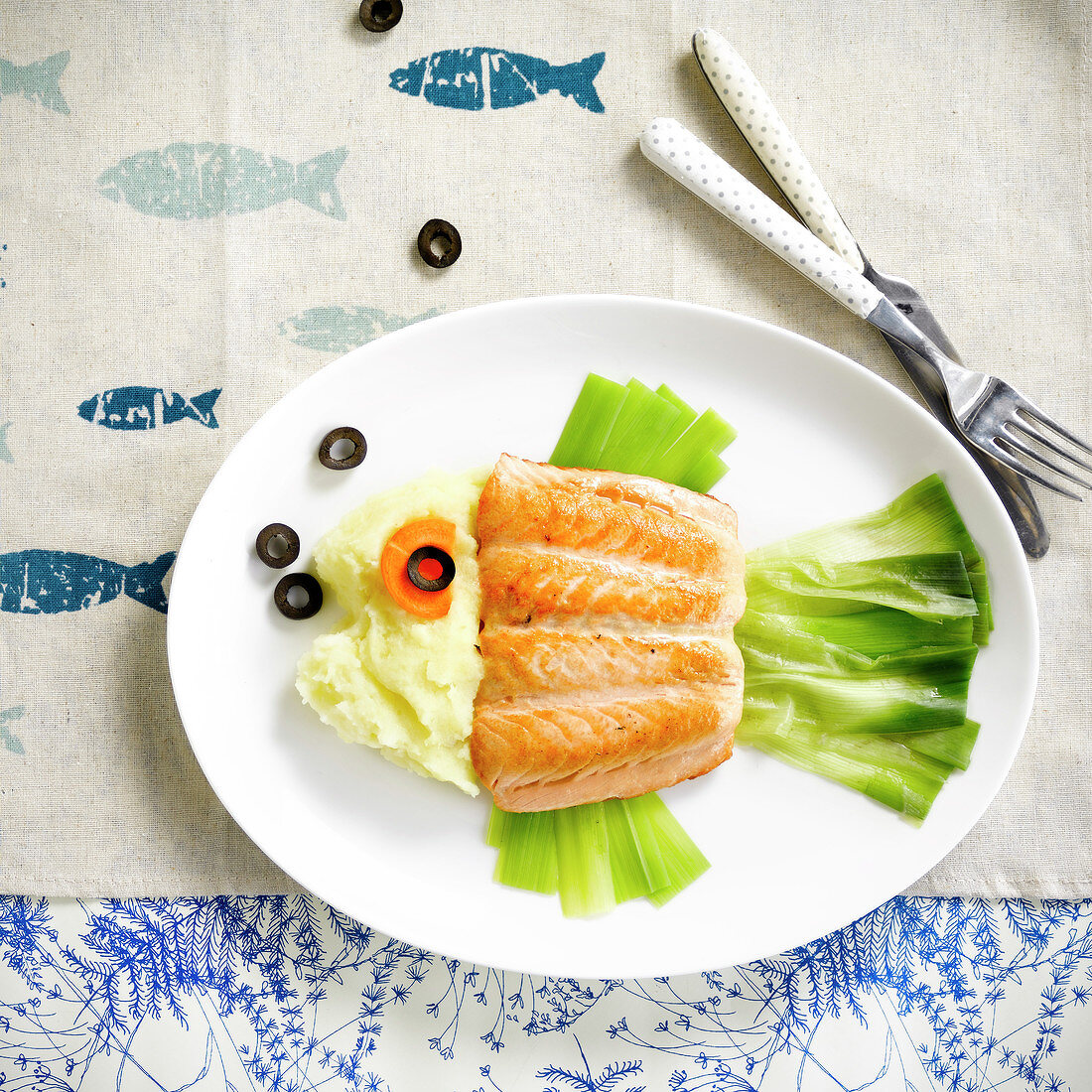 Fish-shaped plate of salmon, leeks and black olives