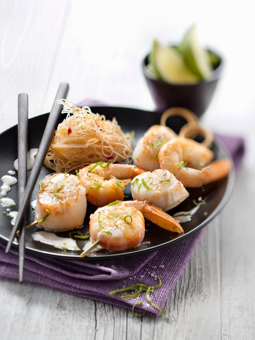 Skewers of scallops and gambas marinated in coconut milk and lime, vermicelli with chili peppers