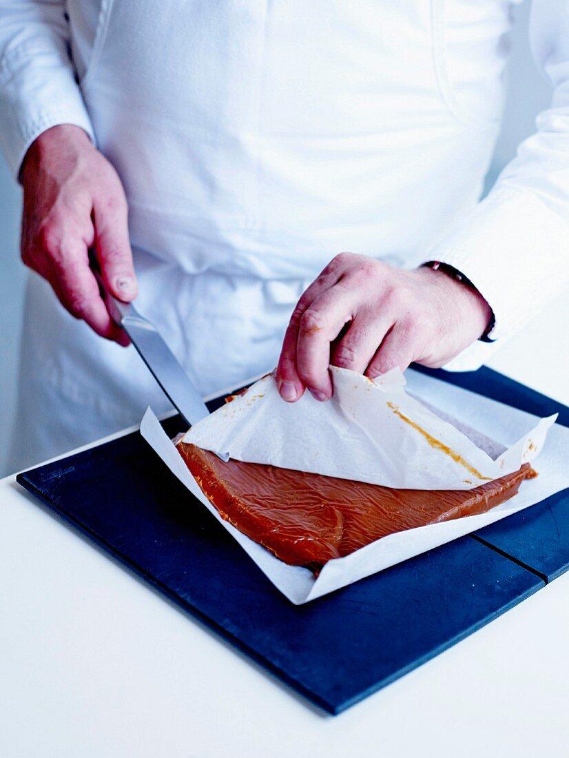 Salzbutterkaramellkonfekt herstellen: Backpapier vom Karamell abziehen