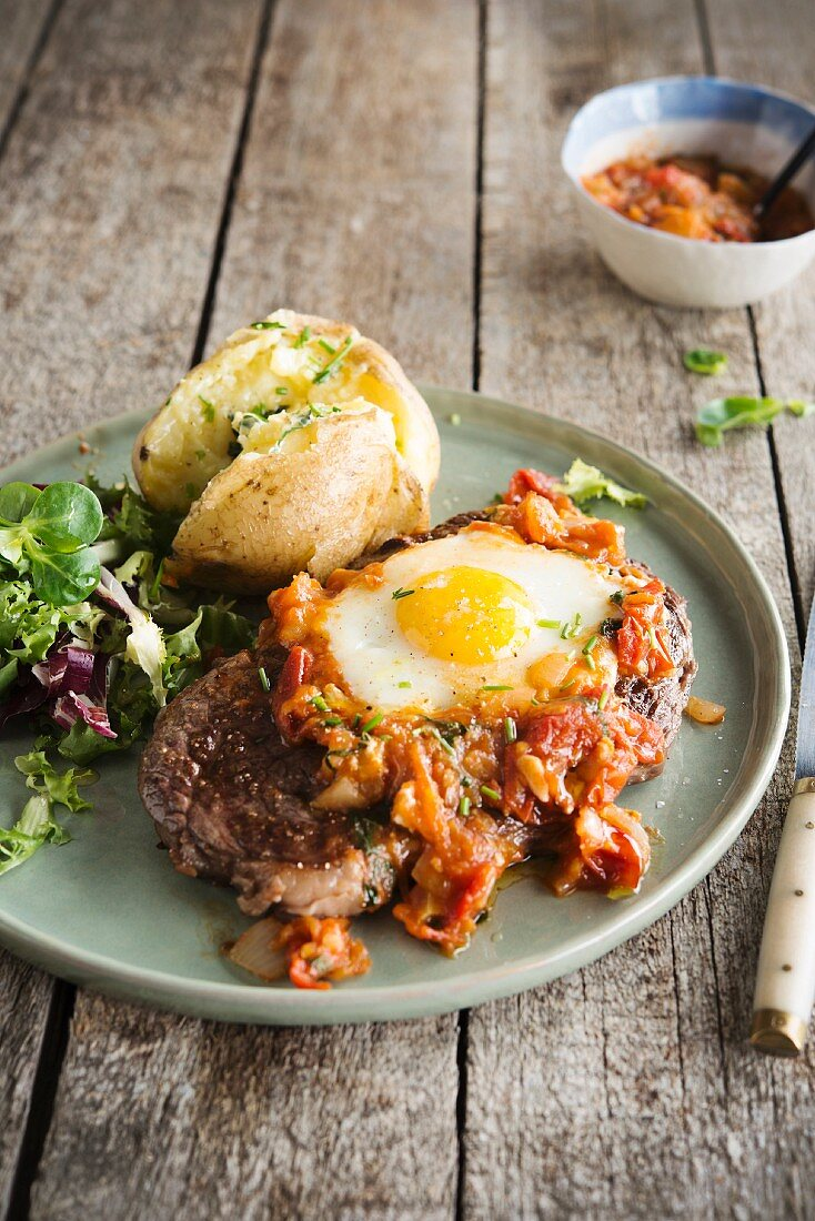 Grilled steak topped with stewed tomatoes and onions and a fried egg, Baked potato with herbs, salad