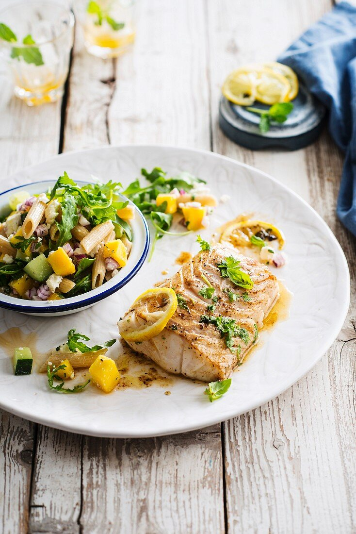 Roasted cod fillet with confit citrus and basil, pasta, cucumber, mango and feta salad