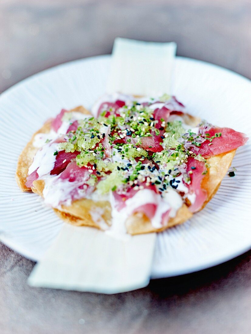 Red tuna sashimi, red onion, flying fish roe revisited crisp pizza with wasabi and two sesame seeds