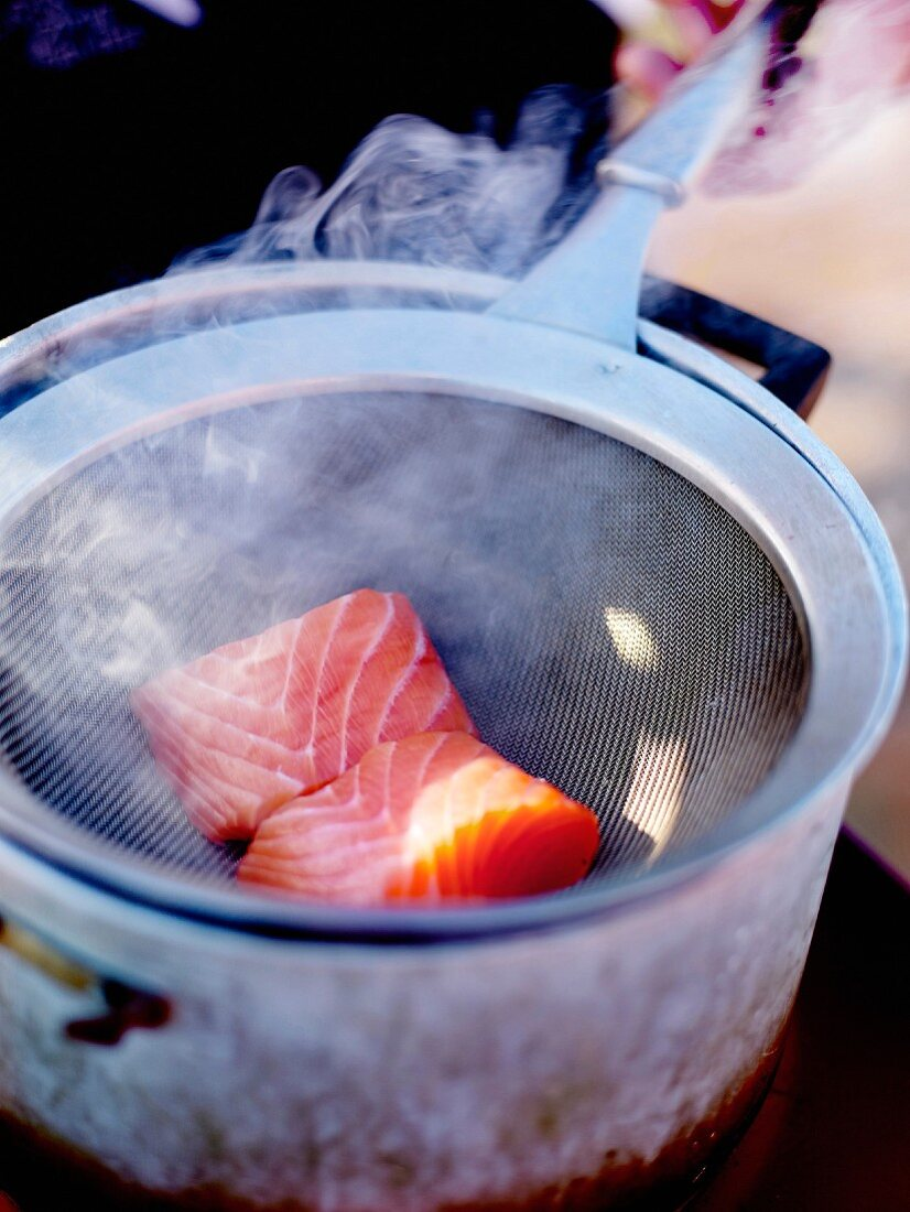 Smoking salmon at home in a casserole with hay