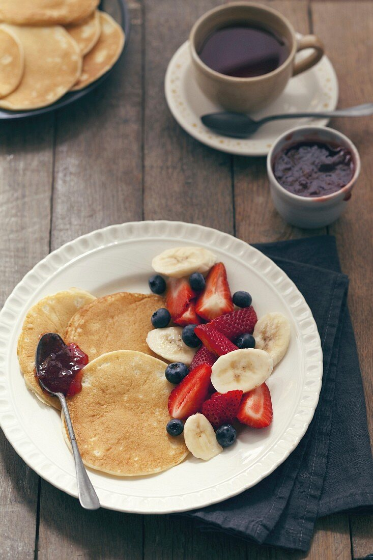 Pancakes with summer berry jam and fresh fruit salad