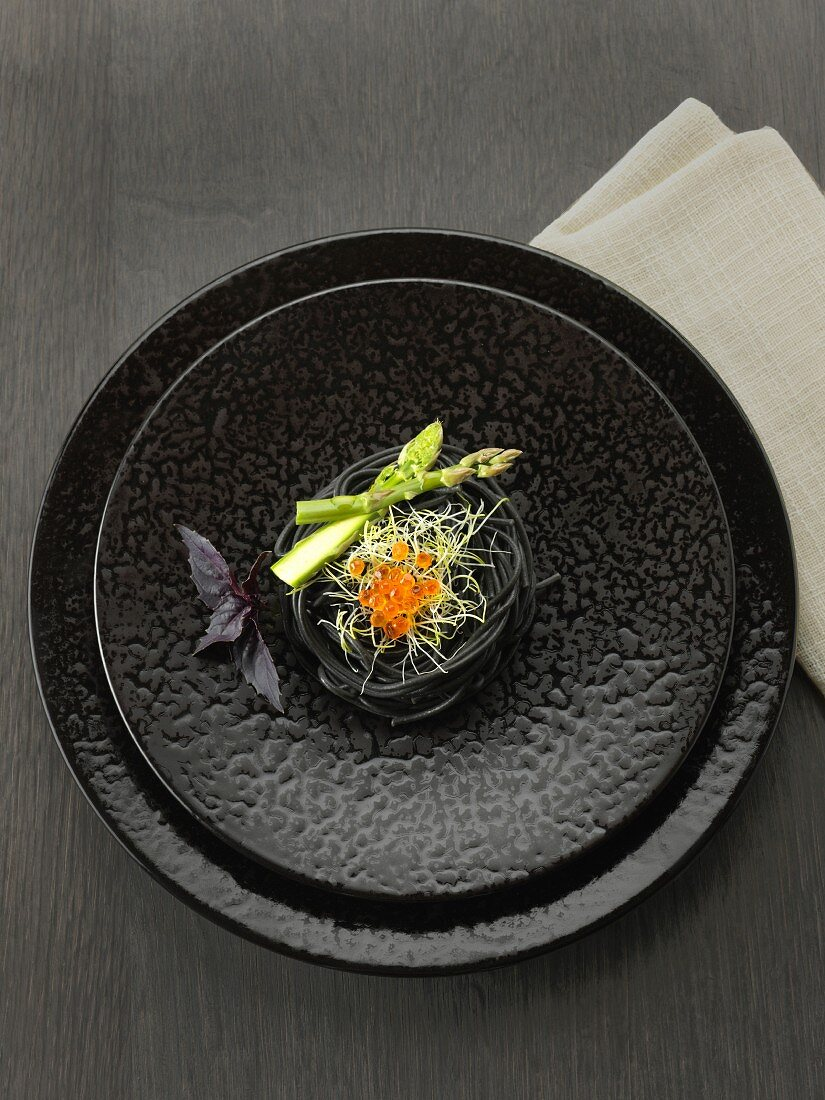 Squid ink spaghettis, green asparagus tops, sprouts and salmon roe