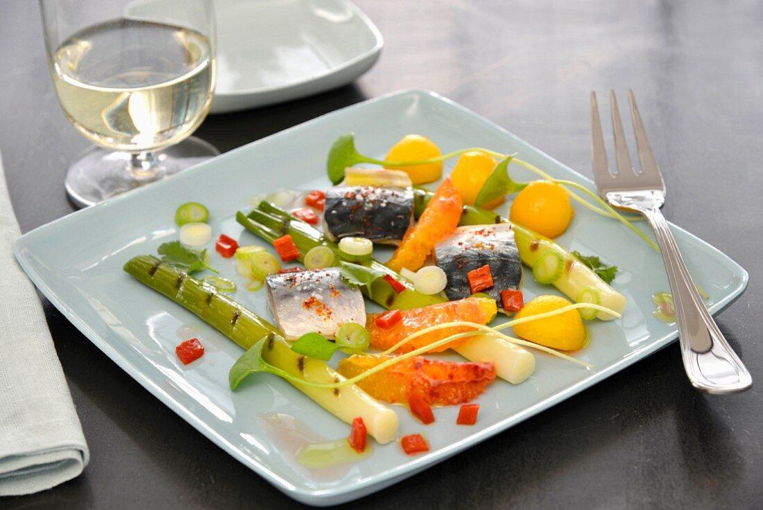 Plate of leeks with red pepper vinaigrette, mackerels, orange segments and small melon balls