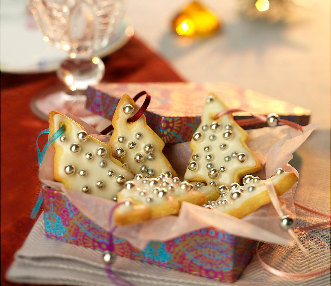 Christmas tree shortbread biscuits decorated with icing and silver sugar pearls