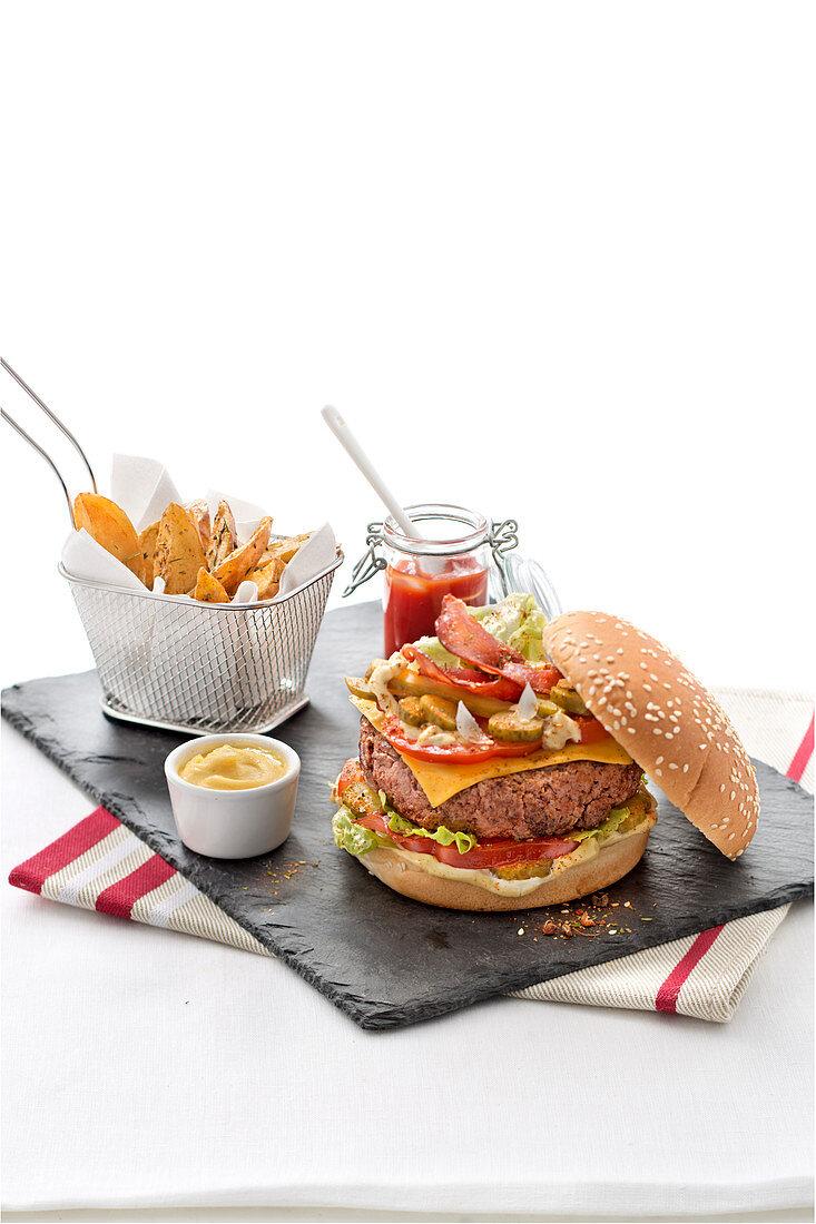 Cheeseburger and potatoes on slate