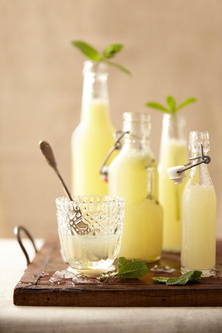 Glass and bottles of homemade lemonade