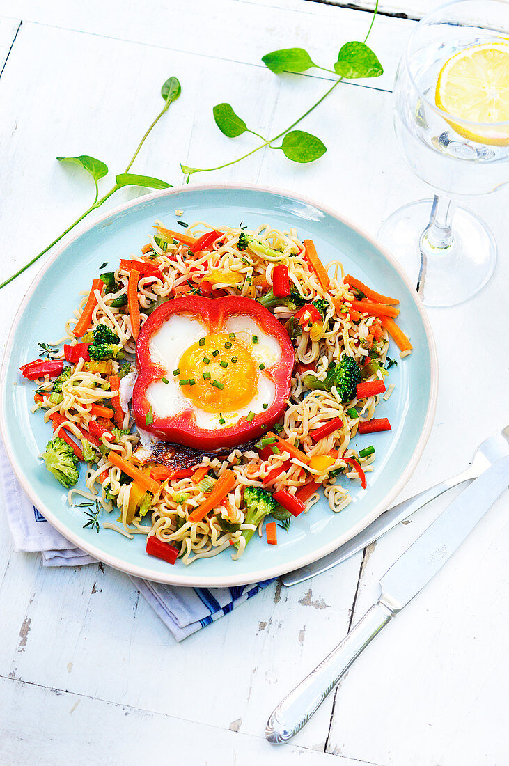 Noodles with vegetables and an egg cooked in half a red pepper