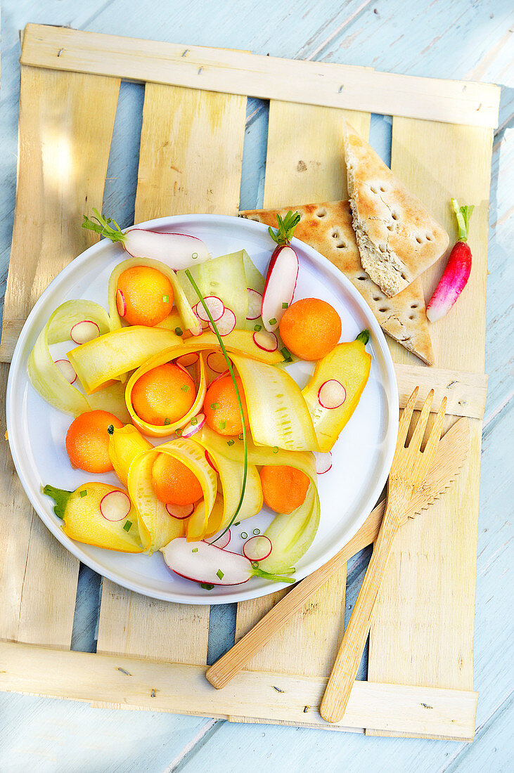 Thin strips of yellow courgettes,cucumber,radish and melon ball salad