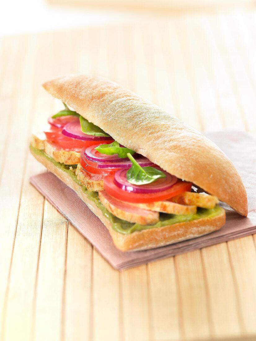 Chicken, tomato, red onion, baby spinach and guacamole ciabatta bread sandwich