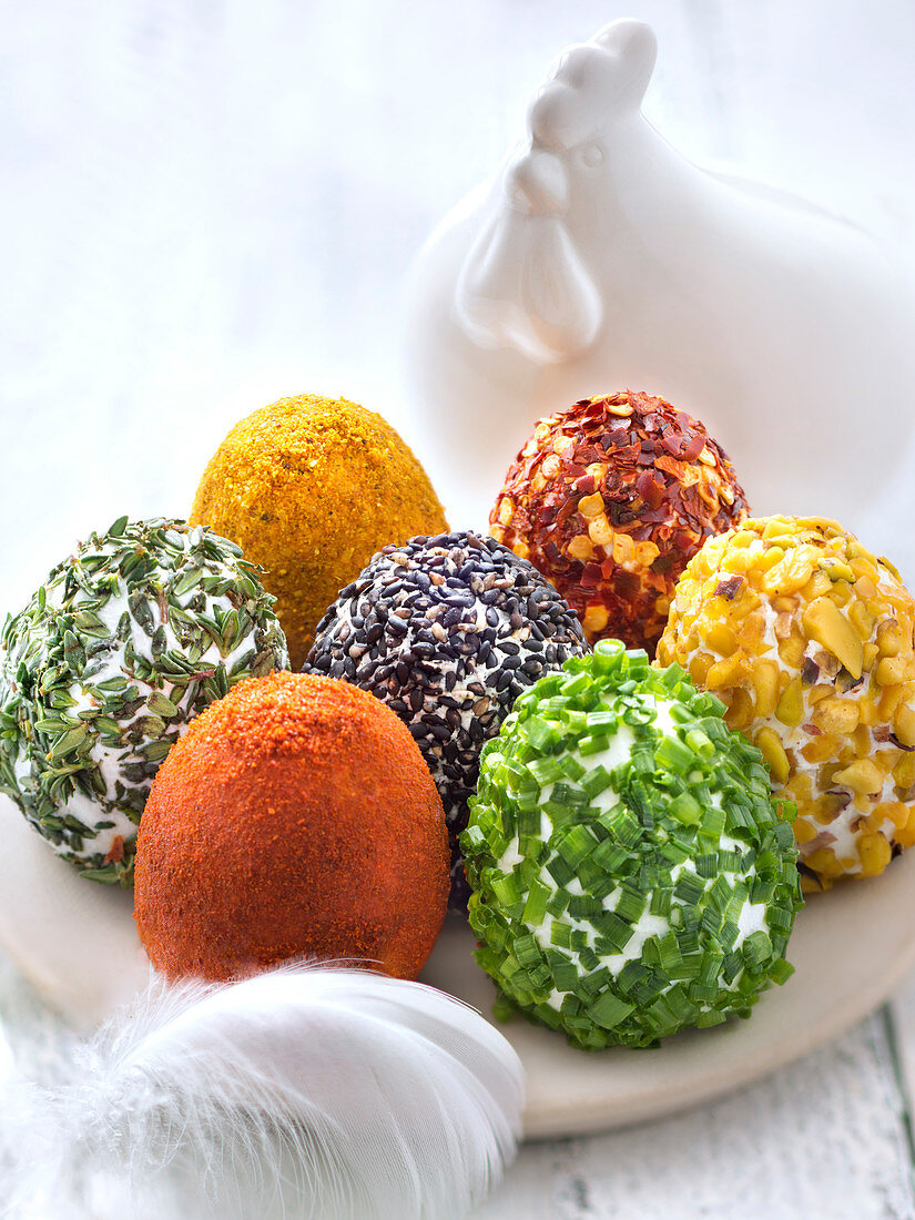 Selection of fresh goat's cheese shaped eggs coated in different spices and herbs