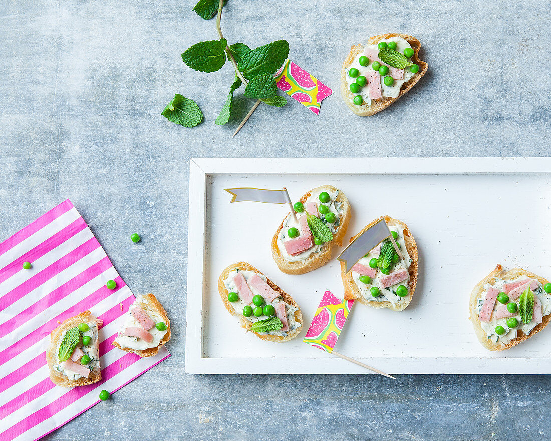 Canapés of fresh cheese with ham, peas and mint