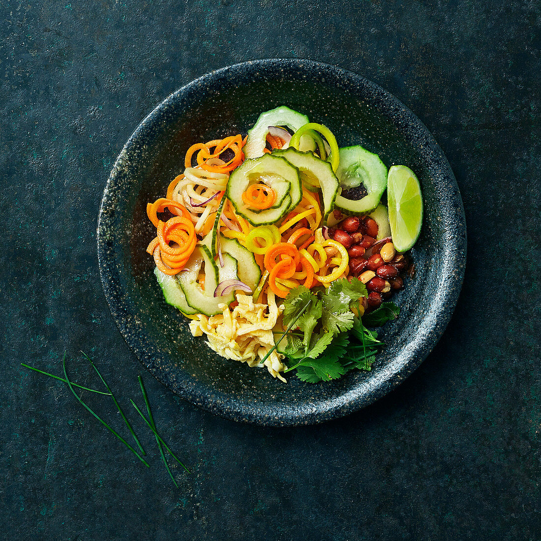 Vegetable spaghetti with omelette, peanuts, coriander and lime