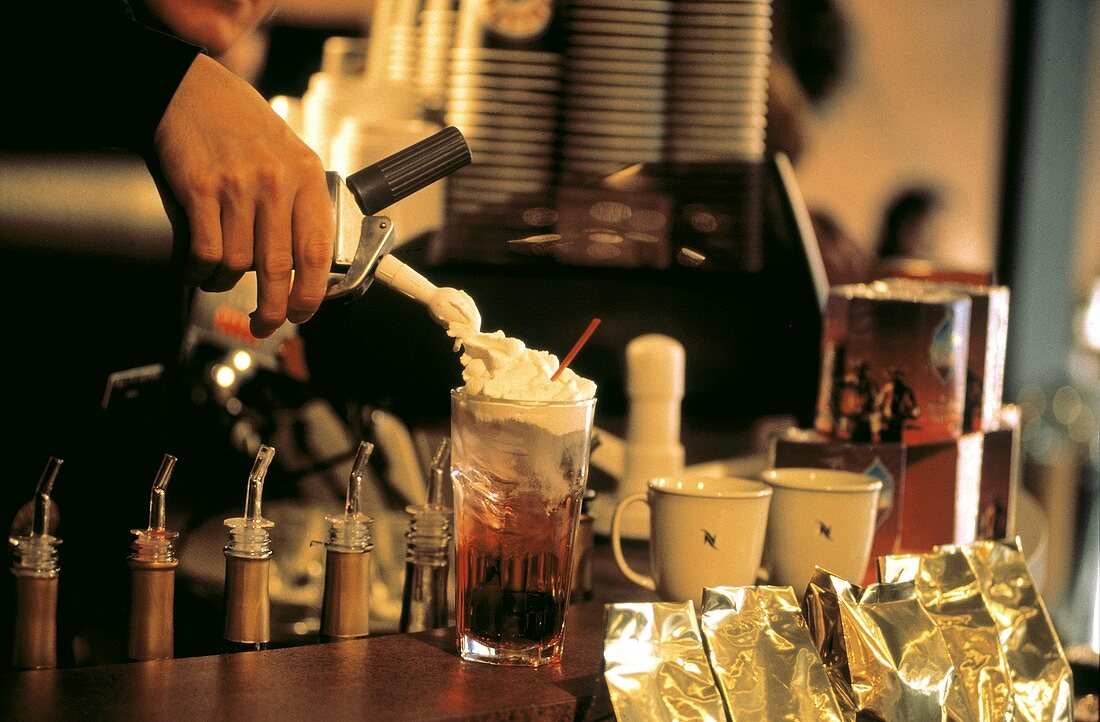 Waiter Topping Drink with Whipped Cream